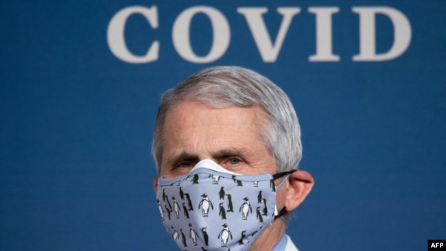 (FILES) In this file photo White House Chief Medical Adviser on Covid-19 Dr. Anthony Fauci listens as US President Joe Biden (out of frame) speaks about the 50 million doses of the Covid-19 vaccine shot administered in the US during an event commemorating