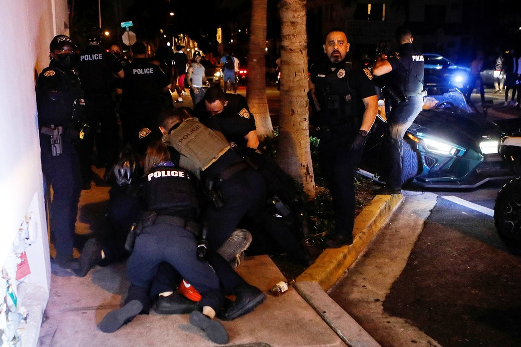 At least 6 police officers tackle a person on the ground, unseen