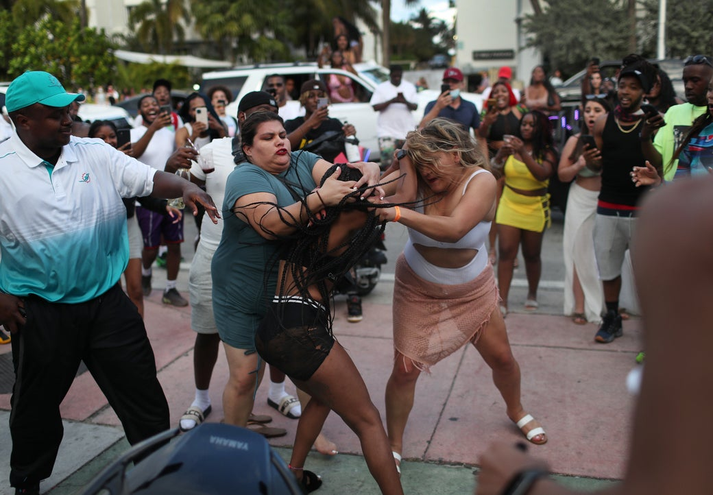 Three women fight while the crowd films it